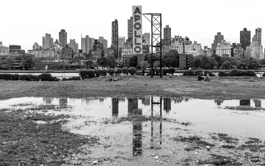 Apollo is standing while others are sitting! Apollo Architecture Art Installation Astoria Park Blackandwhite Building Exterior Built Structure City Cityscape Clear Sky Day Outdoors Real People Reflection Skyscraper Water
