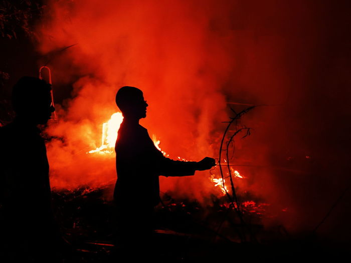 Silhouette man against orange fire at night