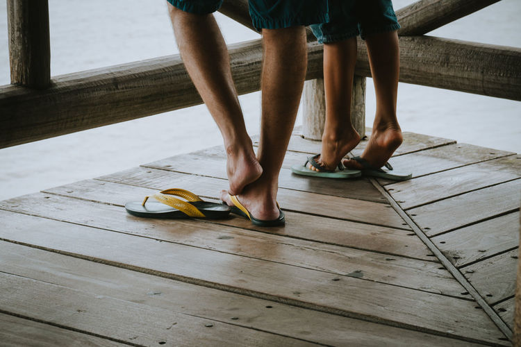 Low section of people wearing flip-flops on wooden floor