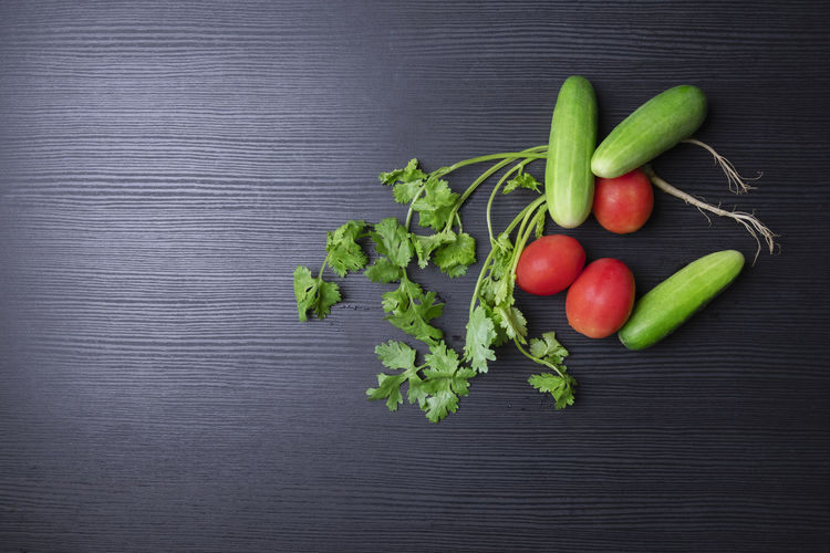 A group of fresh vegetable cucumber tomato and coriander on wood table Diet Red Black Background Choice Close-up Coriander Directly Above Food Food And Drink Freshness Fruit Green Color Healthy Eating High Angle View Indoors  No People Organic Raw Food Still Life Table Tomato Variation Vegetable Vegetarian Food Wellbeing