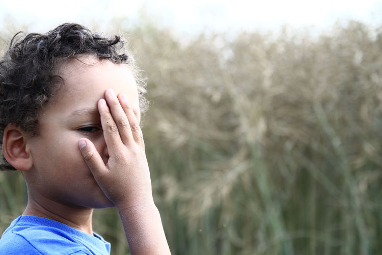 Close-up of boy covering face while standing against plants