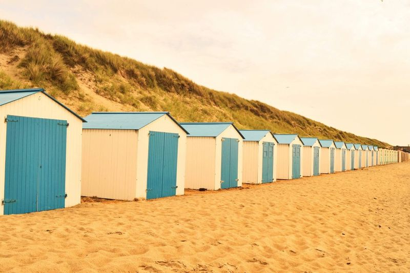 Beach huts by sea against sky