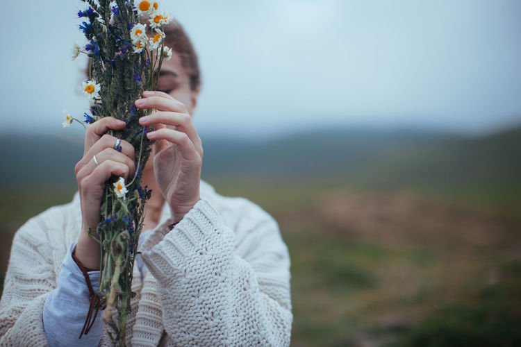 Close-Up Of Woman Holding Flower On Field Against Sky