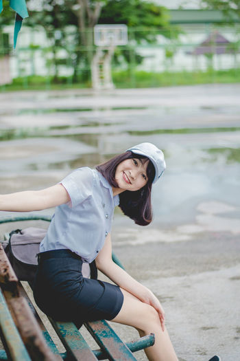Portrait of smiling young woman sitting on bench in park during rainy season