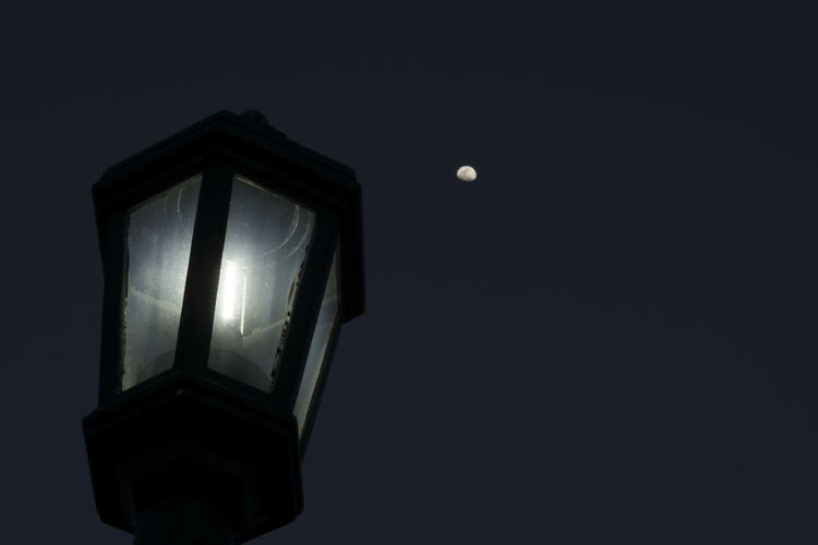 Shot of street light and moon in background February Key West Mallory Square Architecture Close-up Copy Space Dark darkness and light Electric Lamp Electricity  Geometric Shape Glowing Illuminated Light Light - Natural Phenomenon Lightbulb Lighting Equipment Low Angle View Man Made Object Moon Nature Night No People Sky Skyward View