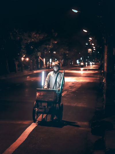 Portrait of man on illuminated street at night
