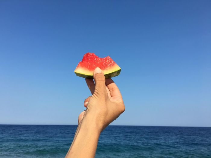 Cropped Hand Holding Watermelon Slice By Sea Against Clear Blue Sky
