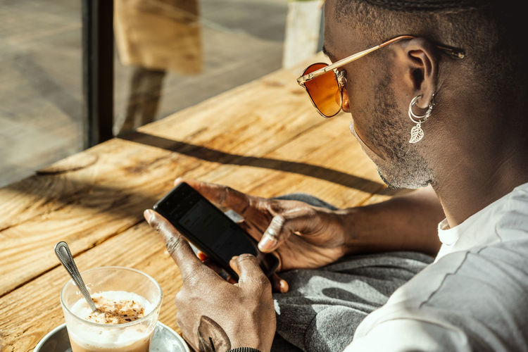 Midsection of man using mobile phone while sitting on table