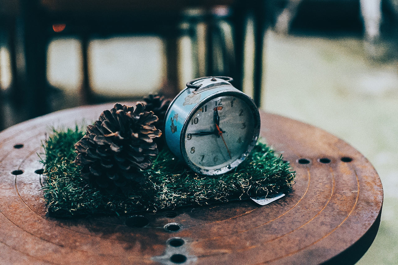 CLOSE-UP OF CLOCK ON TABLE AT HOME