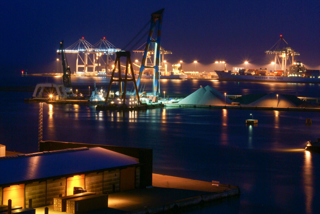 night, illuminated, transportation, nautical vessel, water, harbor, commercial dock, freight transportation, mode of transport, reflection, no people, shipping, sea, industry, outdoors, built structure, moored, sky, cargo container, architecture, shipyard, city, nature