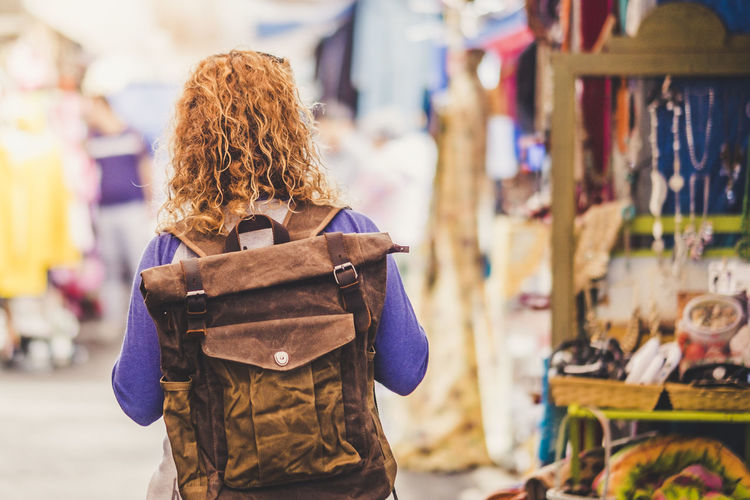 Blonde curly hair woman backpacker traveler viewed from rear at used market enjoying the shopping and alternative vacation - leather backpack view for travel concept One Person Focus On Foreground Real People Hairstyle Women Hair Market Leisure Activity Lifestyles Retail  Adult Curly Hair Day Waist Up Standing Rear View City Incidental People Brown Hair Outdoors Warm Clothing Caucasian Casual Clothing Backpack Backgrounds Market Retail  Choosing Consumerism Vacations Alternative Sunlight Morning Springtime