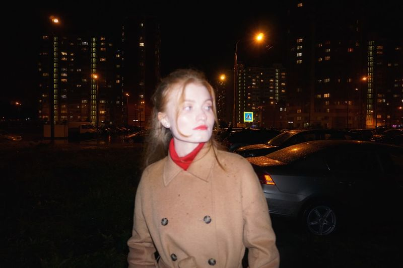 Young woman looking away while standing on street in city at night