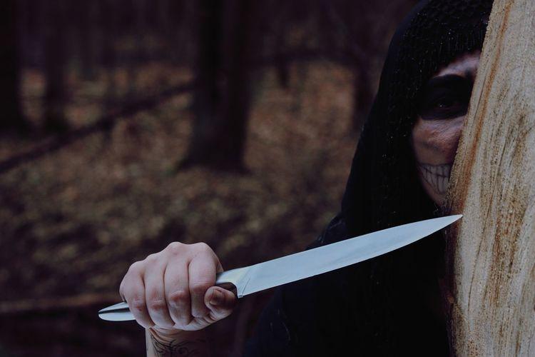 Girl Wearing Skull Mask While Holding Knife During Halloween