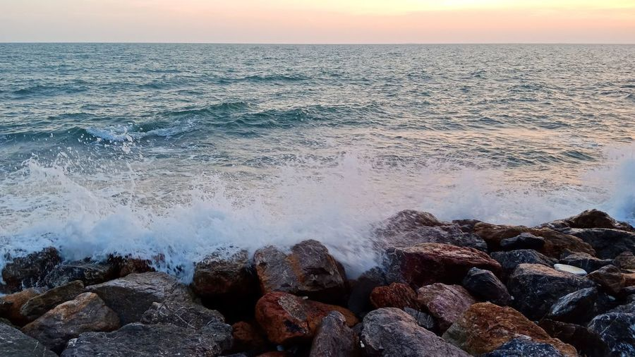 Scenic view of rocks in sea during sunset