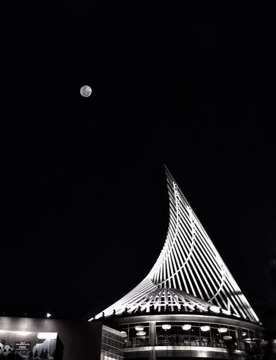 Low angle view of illuminated built structure against sky at night