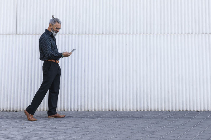 Full length of a man using mobile phone against wall