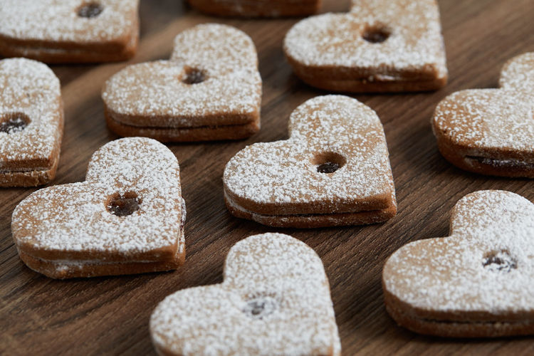 Close up of freshly baked homemade Christmas sugar cookies with jam Food Food And Drink Sweet Food Freshness Indoors  No People Baked Sweet Indulgence Close-up Sugar Wood - Material Choice Variation Temptation Cutting Board Ready-to-eat Selective Focus Focus On Foreground Table Powdered Sugar Homemade Freshness Jam Freshly Baked Freshly Cookies Cookie