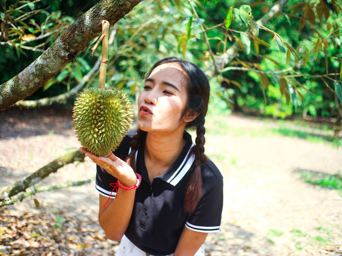 Young woman holding fruit growing on tree