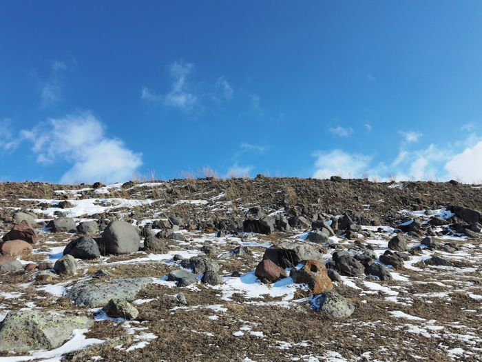 Panoramic view of rocks on landscape against blue sky