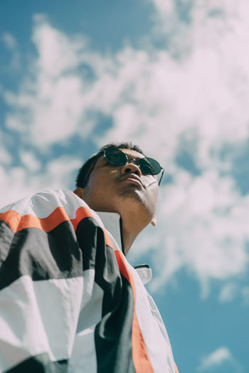 Low angle view of man wearing sunglasses standing against sky