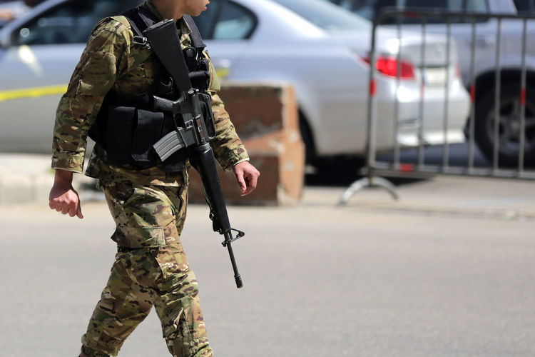 Midsection of soldier walking on road