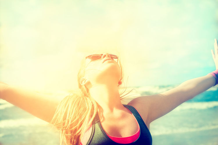 Young woman with arms outstretched at beach against sky