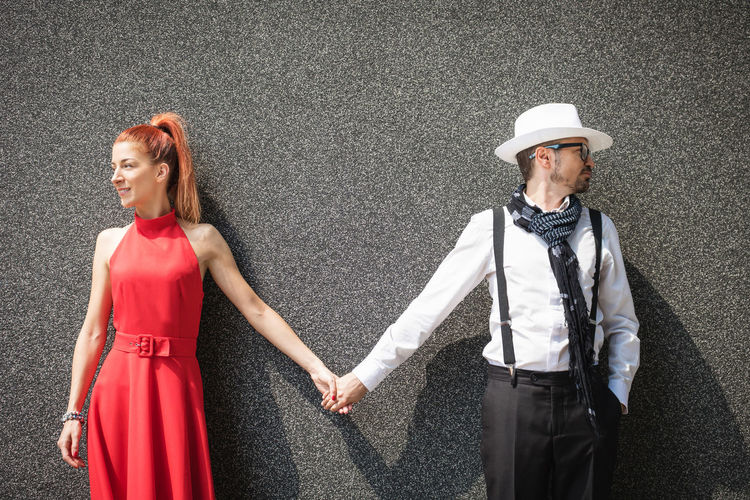 Young couple holding hands against wall while looking away