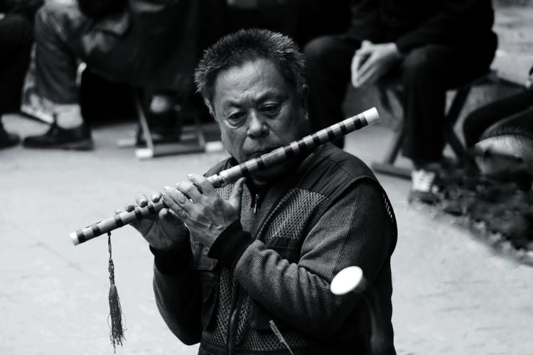 Mature street musician playing flute