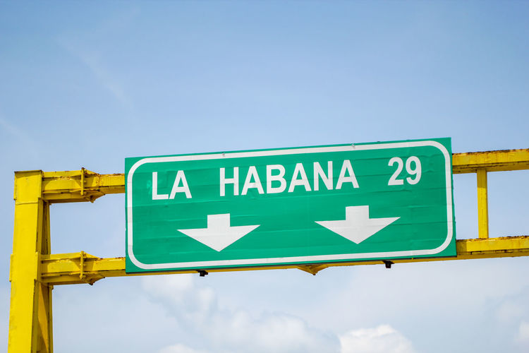 Sky Sign Communication Guidance Text Road Sign Direction Green Color Arrow Symbol No People Directional Sign Day Western Script Low Angle View Symbol Nature Road Information Blue Outdoors Cuba Havana