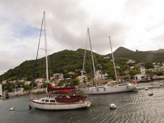 Harbour,Marigot, Saint Martin is typical of Caribbean towns, with gingerbread houses and sidewalk bistros. Boat Caribbean Cloud - Sky Cruise Day Harbor Marigot Mast Mode Of Transport Moored Mountain Mountain Range Nature Nautical Vessel Outdoors Sailboat Sailing Saint Martin Sea Sky Transportation Travel Destinations Vivid International Water Waterfront