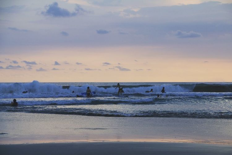 People surfing in sea against sky during sunset
