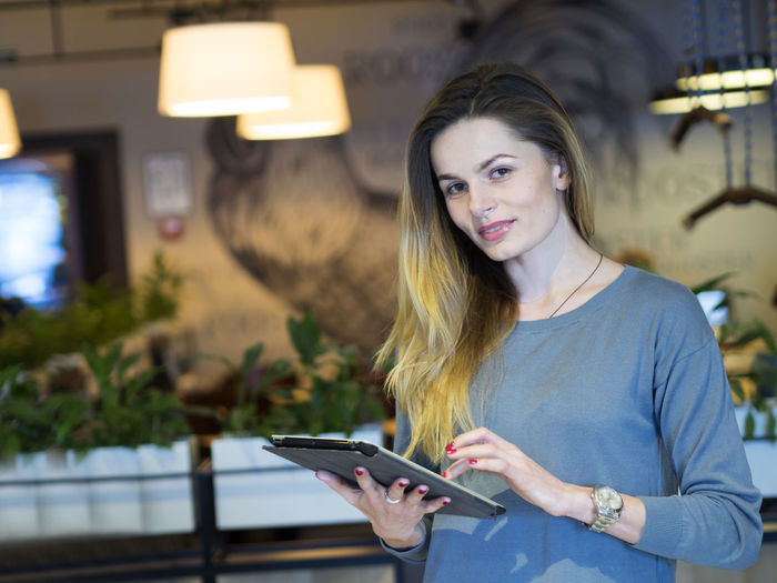 Portrait Of Confident Young Woman With Digital Tablet Standing In Restaurant