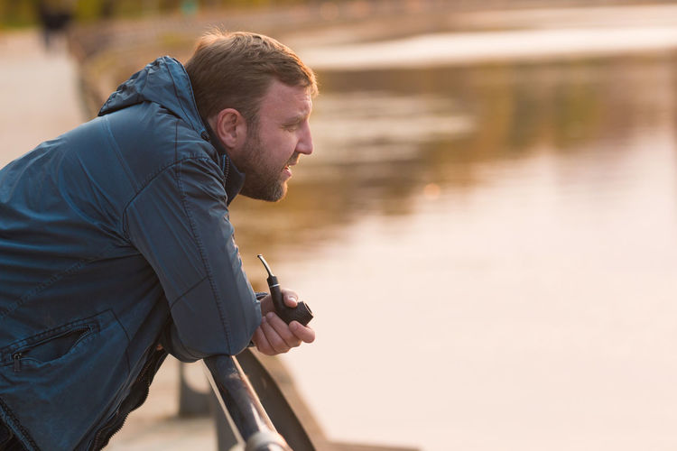 Side View Of Mature Man Smoking While Standing By Railing Against Lake At Park