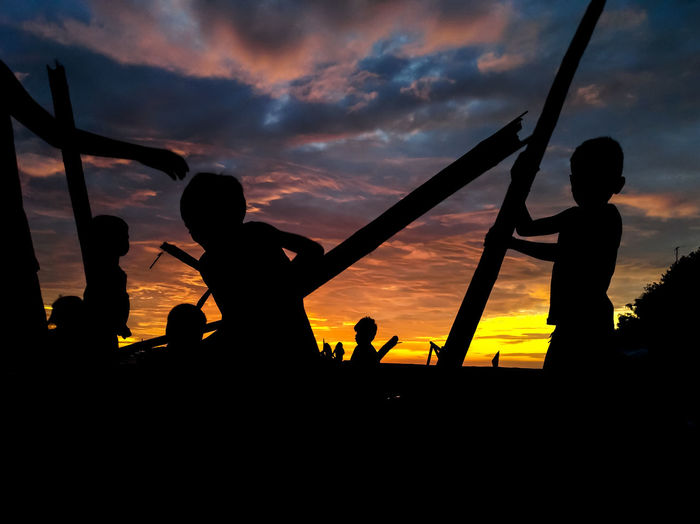 Silhouette people playing against sky during sunset