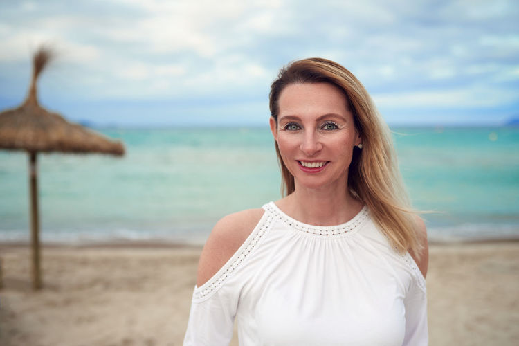 Smiling attractive woman standing at the beach Looking At Camera Woman Beach Beautiful Woman Best Ager Blond Copyspace Focus On Foreground Leisure Activity Looking At Camera Middle-aged Nature One Person Outdoors Portrait Real People Sea Shore Smiling Standing Water