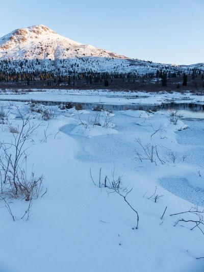 down by the frozen lake Beauty In Nature Blue Blue Hour Canada Clear Sky Cold Temperature Day Frozen Ice Lake Landscape Mountain Mountain Range Nature No People Outdoors Scenics Sky Snow Tranquil Scene Tranquility Water White Color Winter Yukon Territory