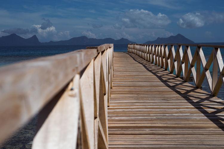 Wooden bridge pier over sea against sky