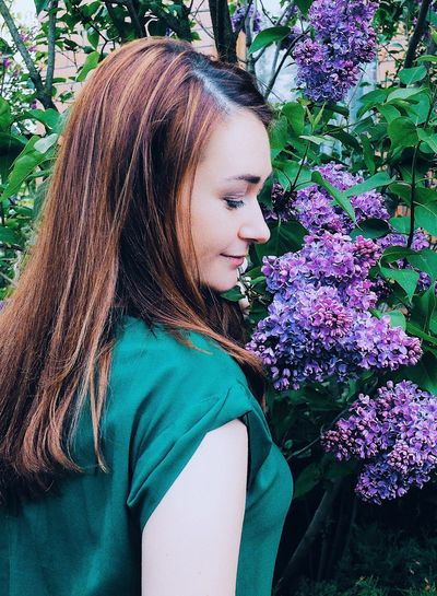 Beautiful young woman with purple flower