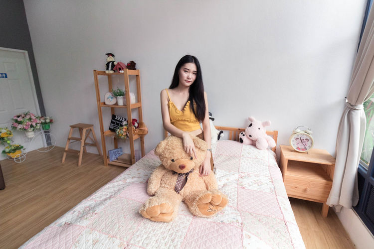 Young woman sitting on toy at home