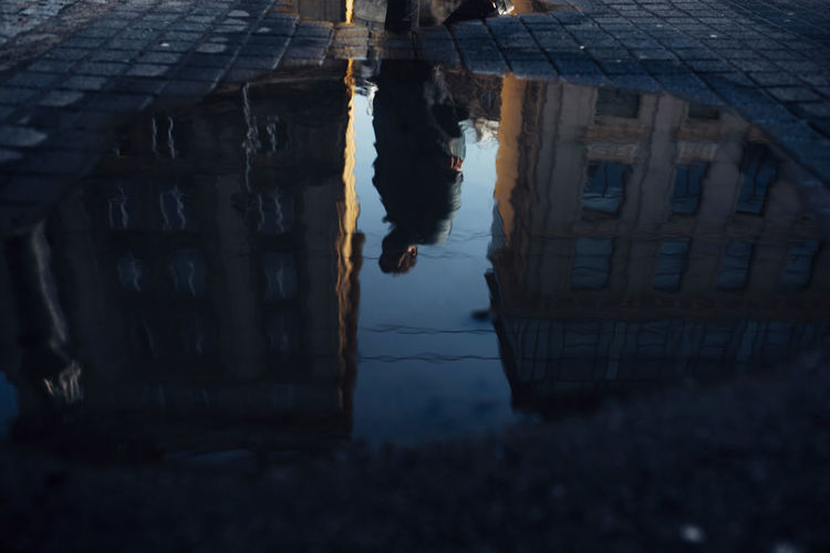 Reflection of woman walking on building in city