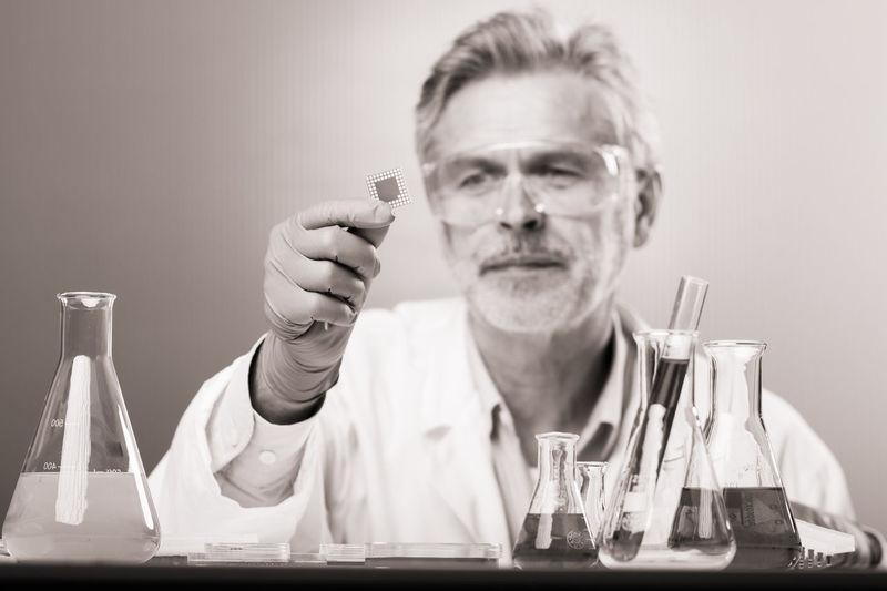 Mid adult man holding eyeglasses
