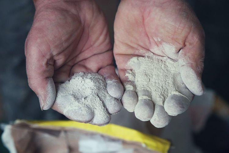 Close-up of cropped worker hands with cement