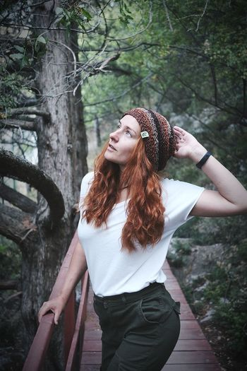 Full length of young woman standing in forest