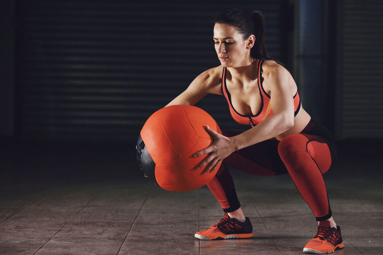 Full Length Of Young Woman Holding Medicine Ball While Squatting In Gym
