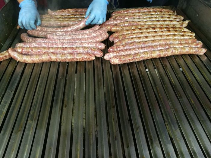 High Angle View Of Person Grilling Asado Sausages On Barbecue