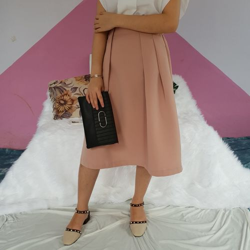 Low Section Of Fashionable Woman Standing On Sheet Against Wall