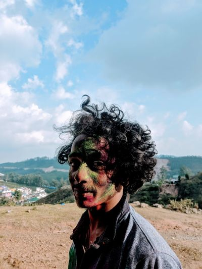 Portrait of man face covered with powder paint against sky
