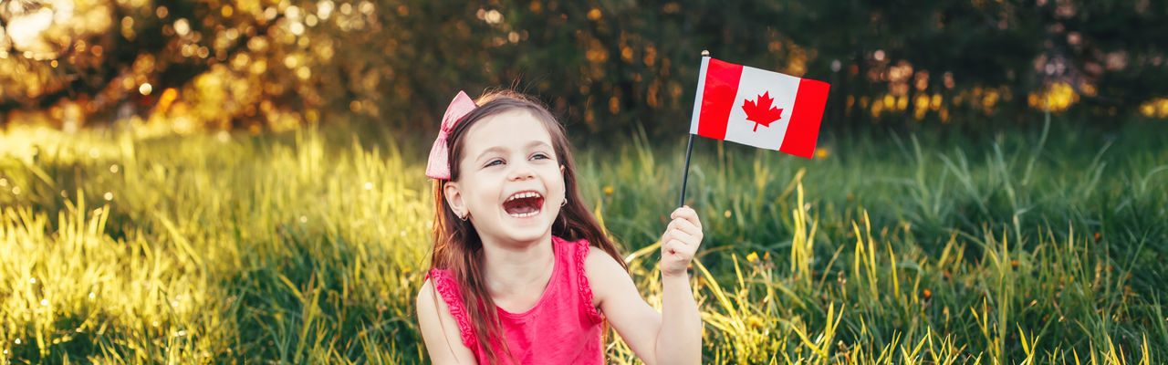 Close-up of smiling girl holding canadian flag sitting outdoors
