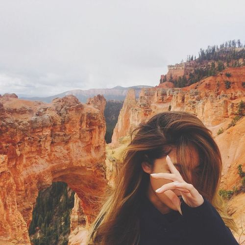 Woman looking at view of rock formations against sky