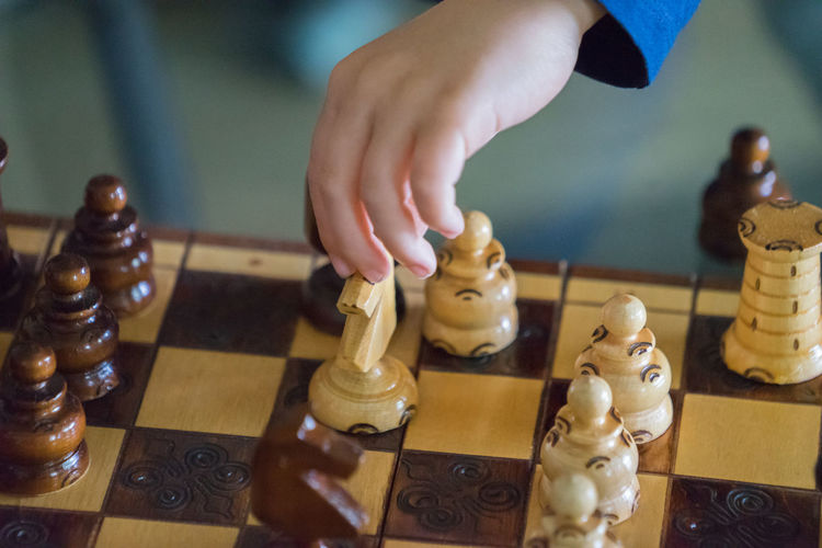 Cropped hand of child playing chess